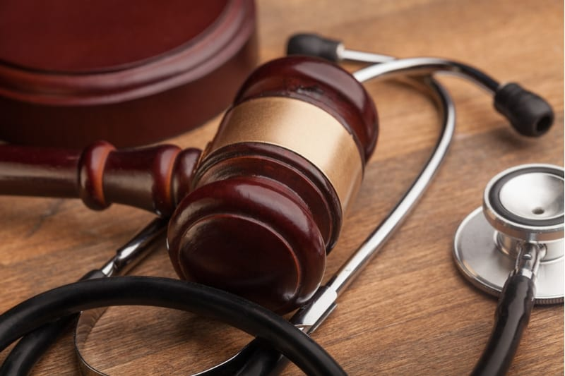Close up of brown gavel and stethoscope on wooden table