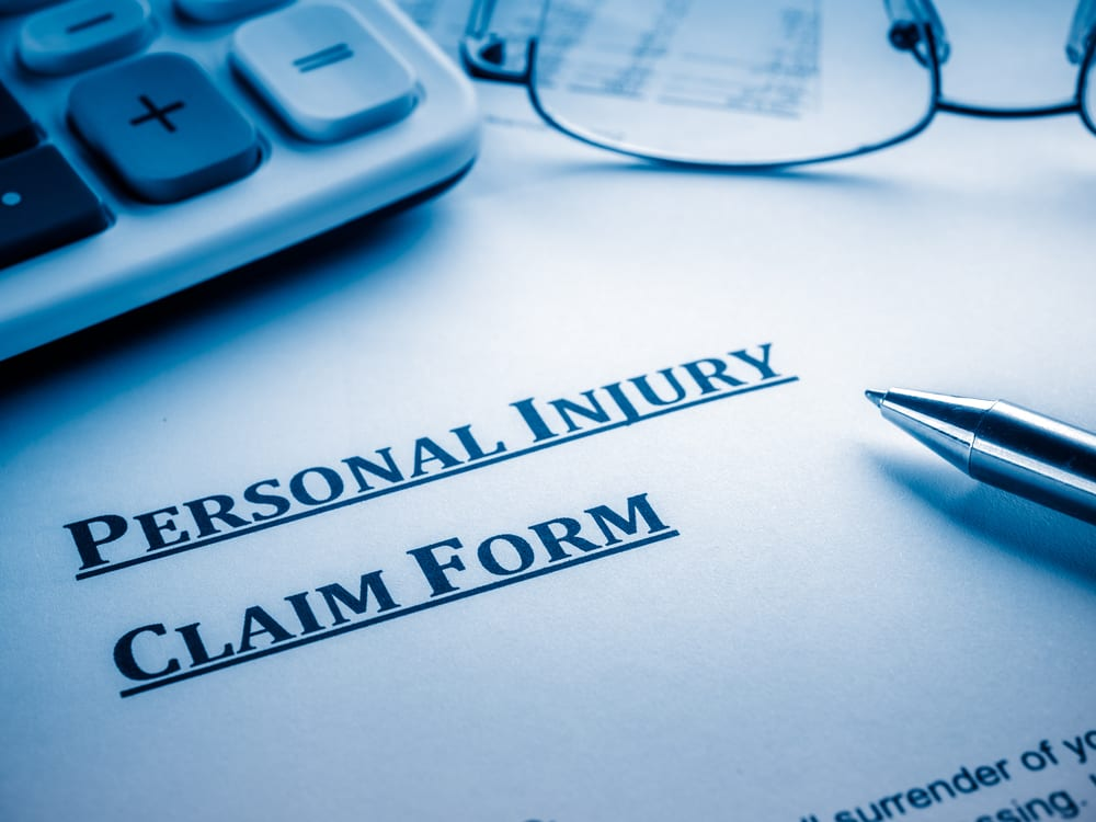 Personal Injury Claim form with calculator, pen, and glasses