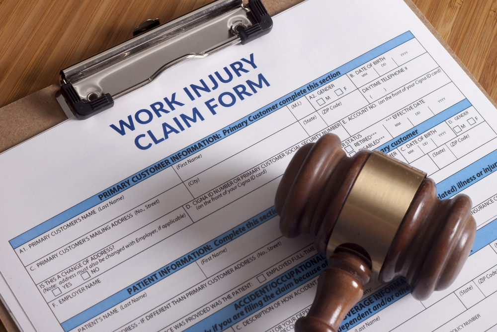 Work Injury Claim form on clipboard on table with wooden gavel