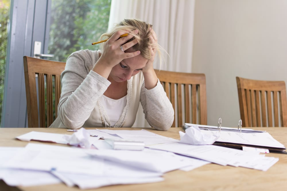 Woman sitting with hands on head looking at stacks of paperwork on table