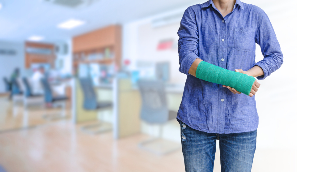 Woman in blue shirt and jeans with green arm cast standing in office space