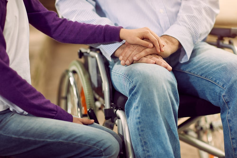 Man sitting in wheelchair holds hands with woman wearing a purple shirt