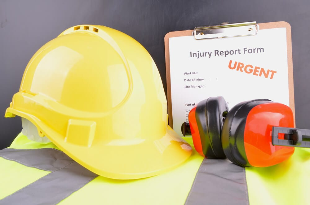 Yellow hard hat, orange ear protectors, yellow safety vest, and injury report form on a clipboard