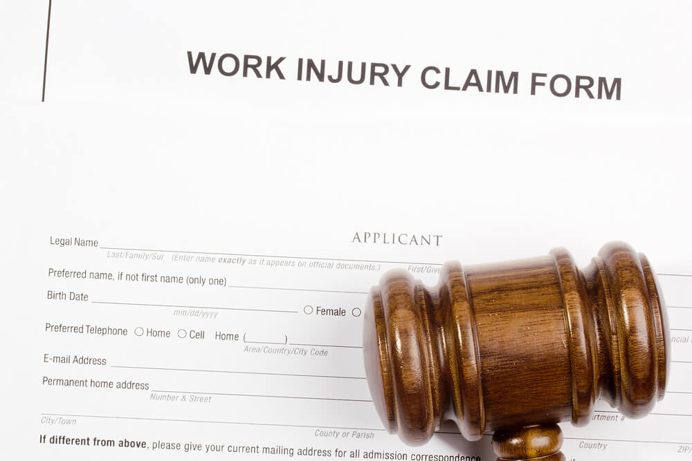 Close up of Work Injury Claim form and wooden gavel