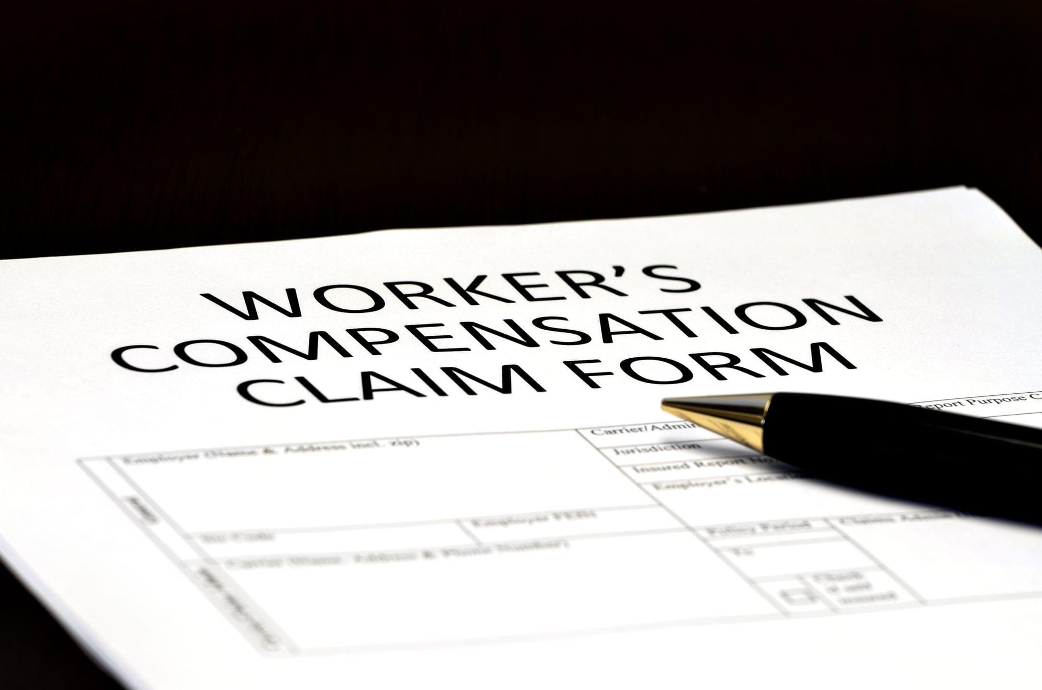 Close up of Worker's Compensation Claim form and black pen