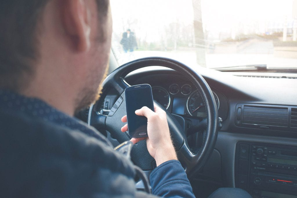 Man sitting behind wheel of car holding smart phone in one hand