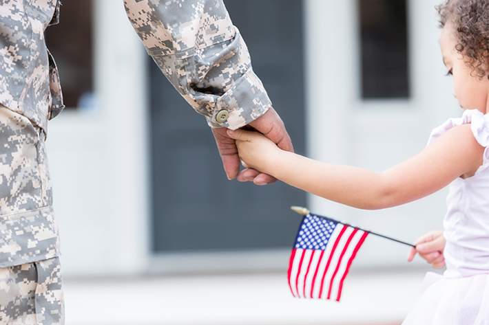 Child in white dress with a small American flag holds hand of military service-member in uniform