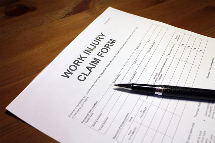 Work injury claim form paper on wooden table with black pen laid on top
