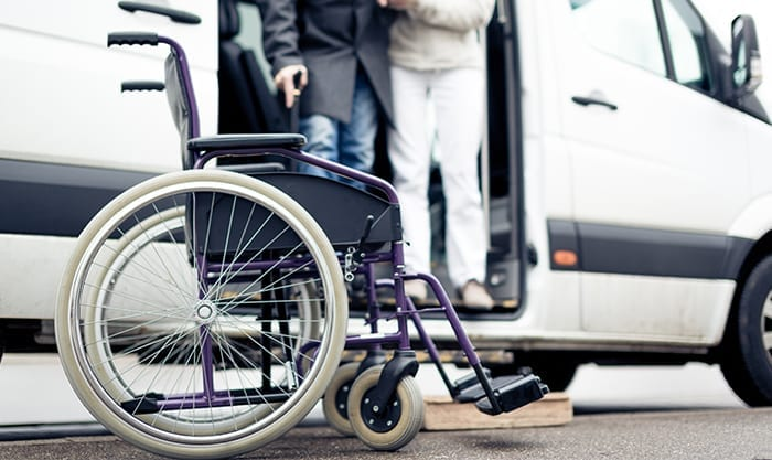 Nurse helping disabled person exit van to get to wheelchair