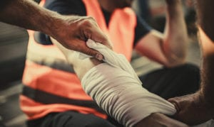 Wounded worker getting their arm wrapped in a bandage.