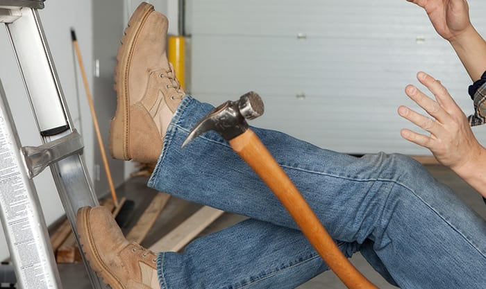 Worker falls off of a ladder in a garage and drops a hammer.