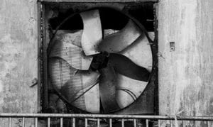 A broken metal industrial fan rests in an abandoned building